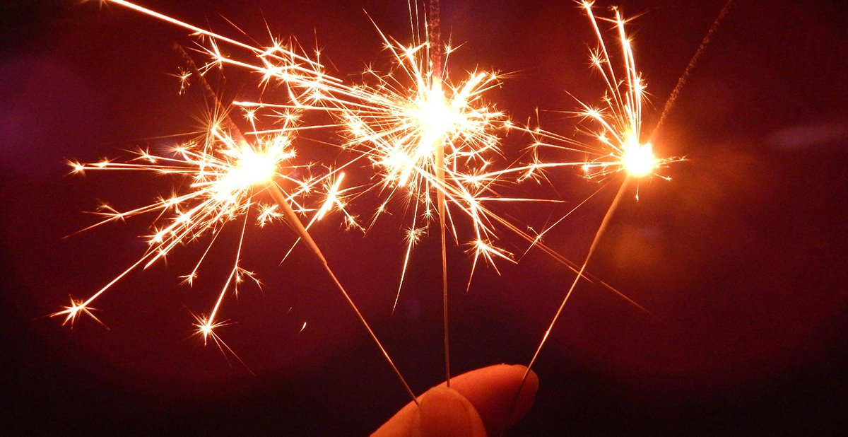 Three sparklers held by two fingers
