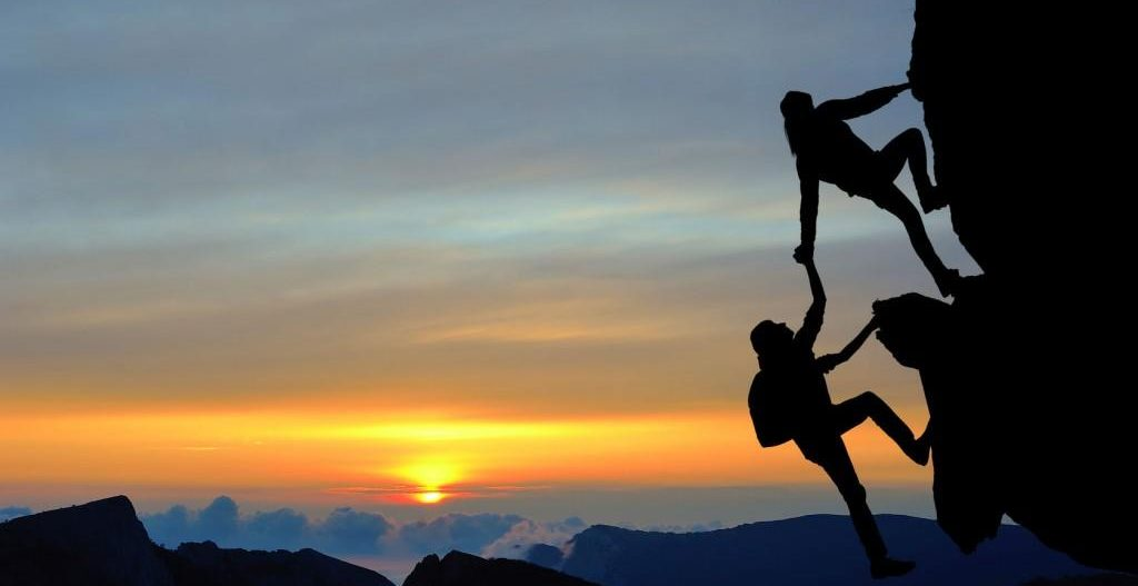 Climber helping another climber on the mountain with sunrise background